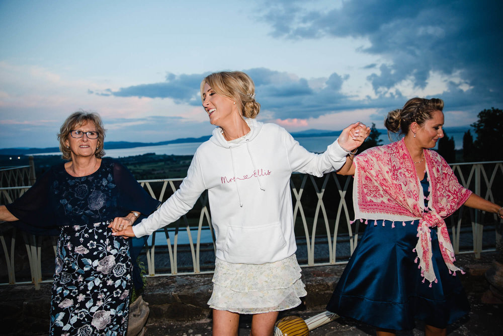 Bride dances with mum and sister with Lake Trasimeno backdrop