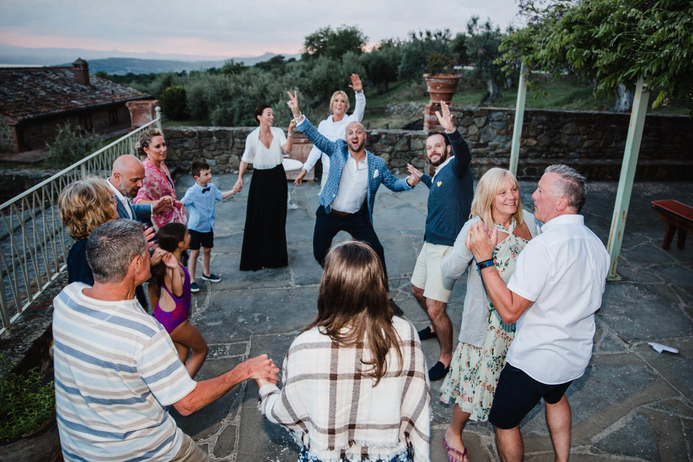 Wide angle photograph of wedding party dancing on terrace balcony of tuscany villa