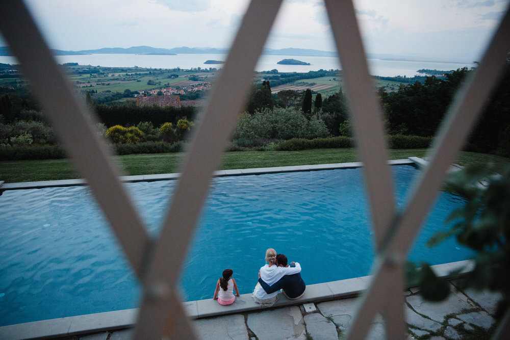 bride and groom hugging while sat in swimming pool looking out at Italian landscape