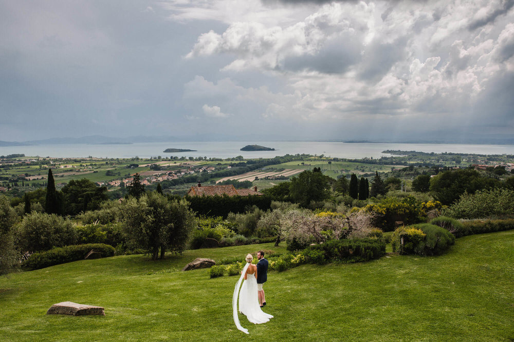 Bride and Groom go for a stroll in their Tuscany garden overlooking Lake Trasimeno