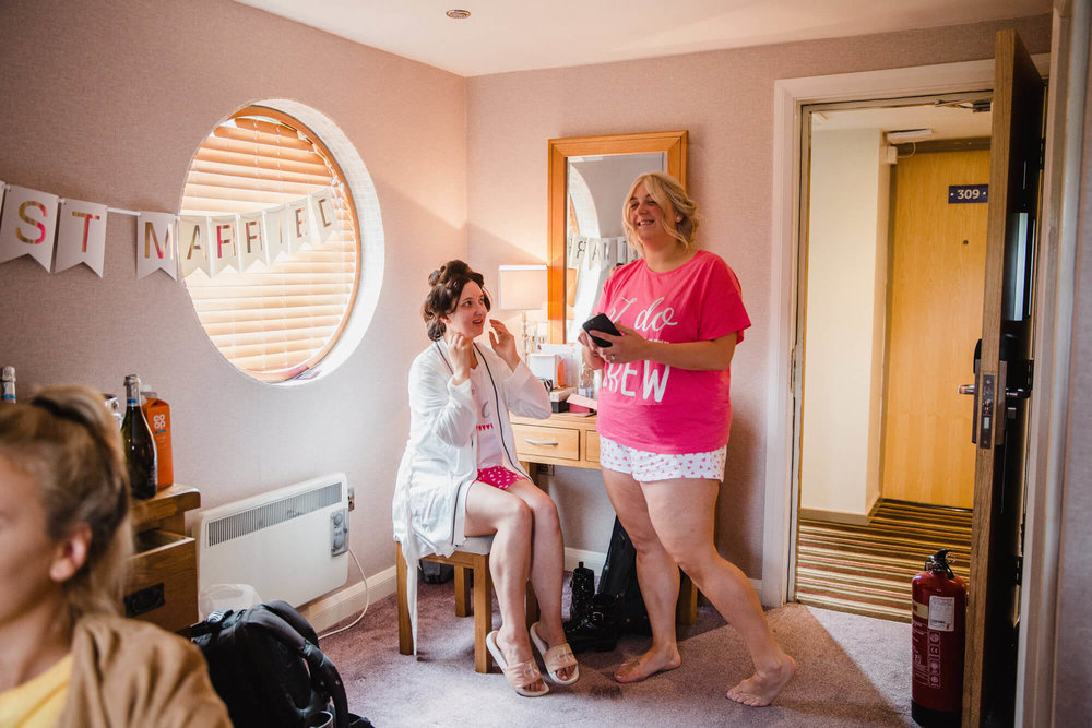 bridesmaid preparing brides make up in morning of wedding at waterside hotel
