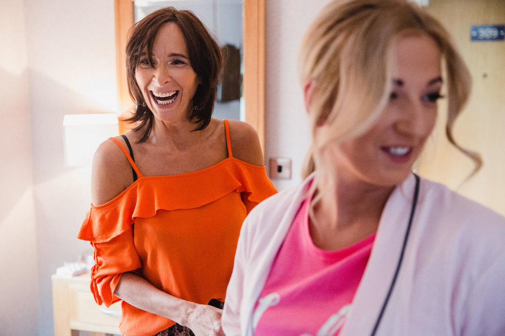 mother of bride laughing and joking with bridesmaid