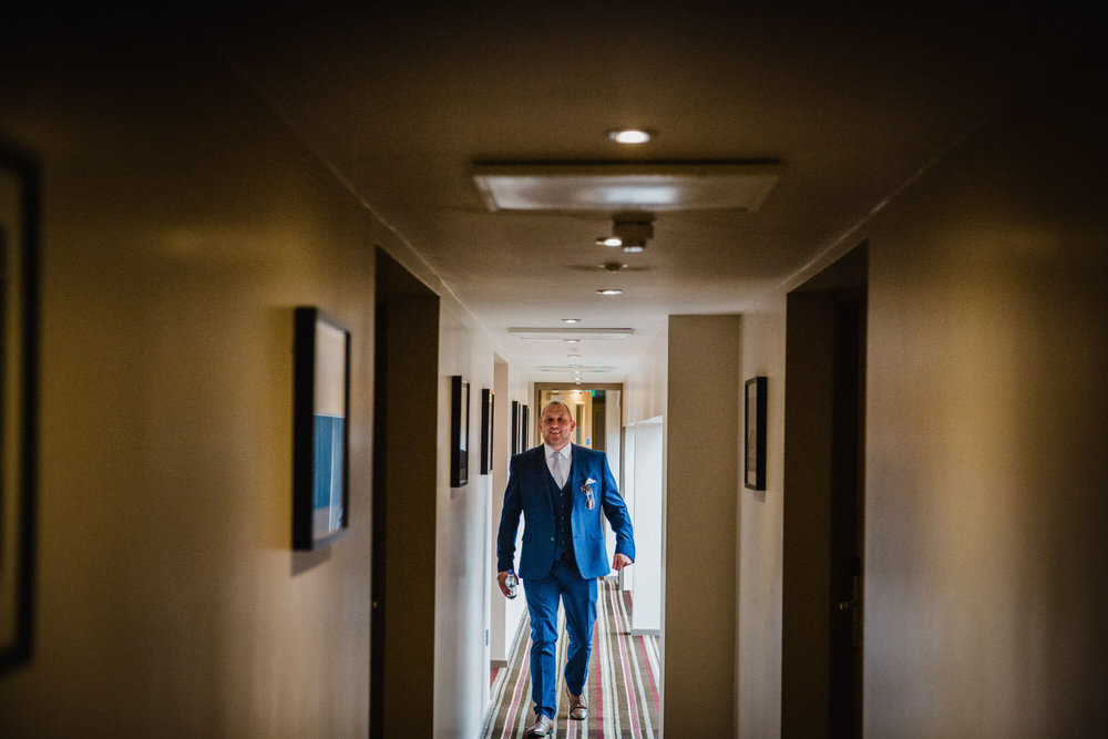 father of bride walking down dark corridor towards camera