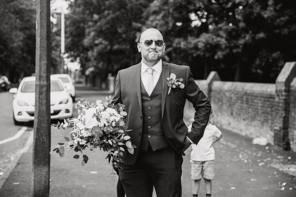 black and white photograph of father of bride holding bouquet of flowers