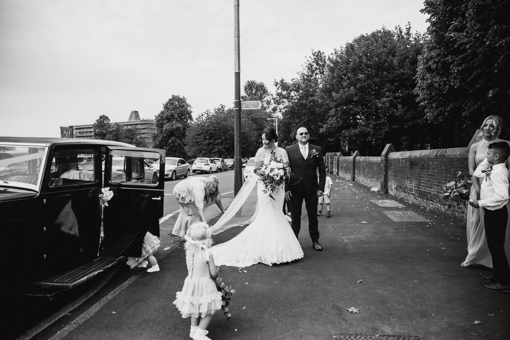 black and white photograph of bridesmaid adjusting veil for dress while bridal party walk to church ceremony