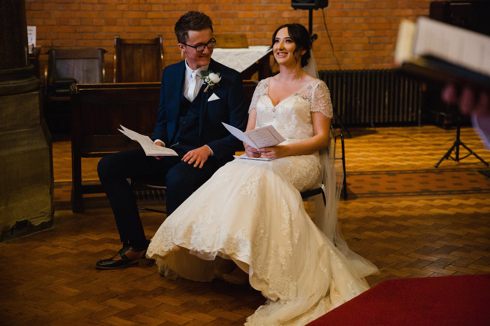 bride and groom sat down on chairs laughing during readings