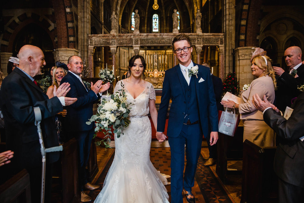 newlyweds walk down aisle to be congratulated by friends and family during ceremony procession