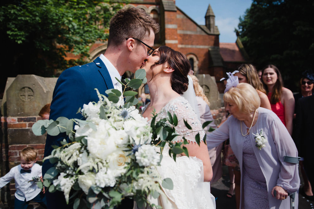 bride and groom share kiss after confetti throwing