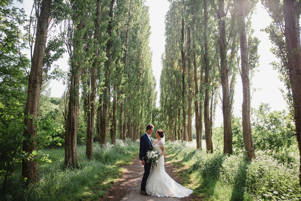 wide angle lens portrait of bride and groom in tree lined pathway in fletcher moss park