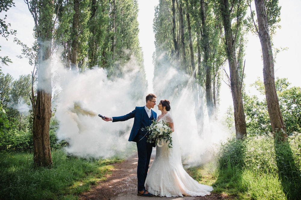 bride and groom portrait at fletcher moss park with smoke grenade
