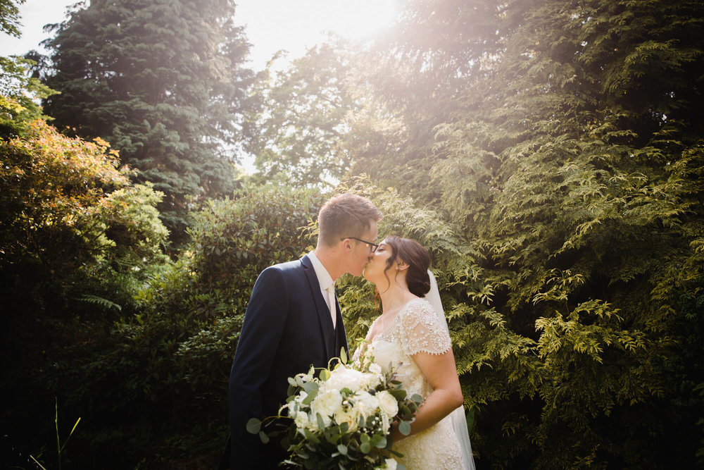 bride and groom kiss with sun flare in lens shining down on couple