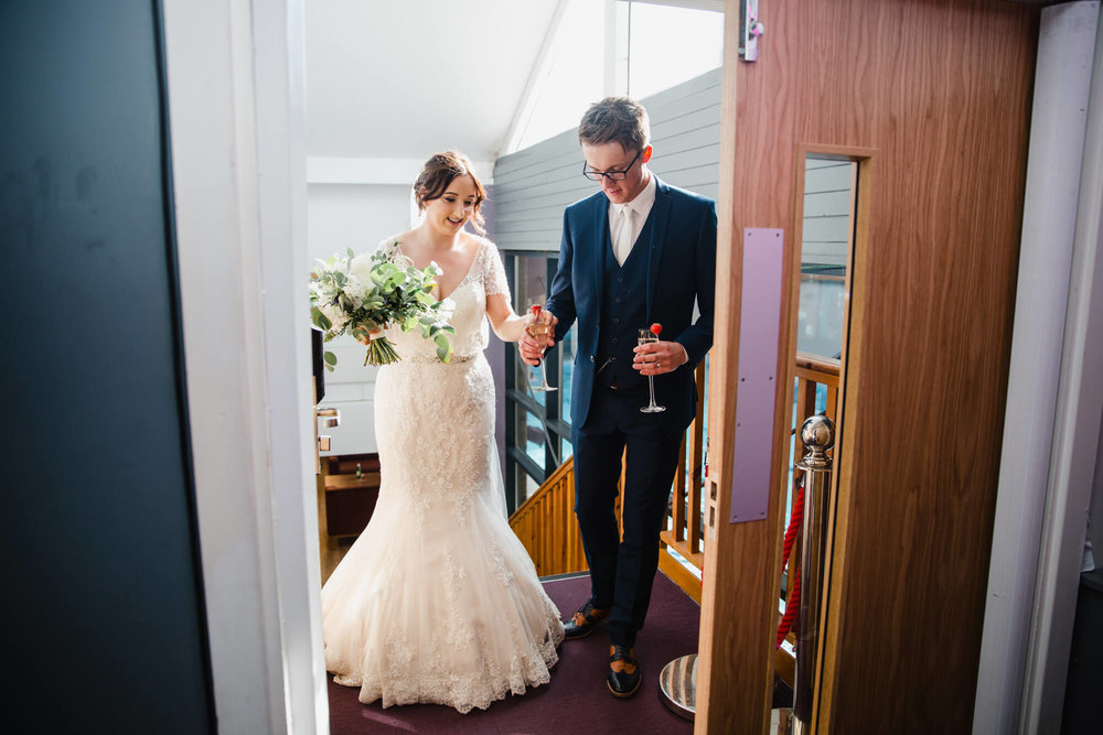 bride and groom entering wedding breakfast room