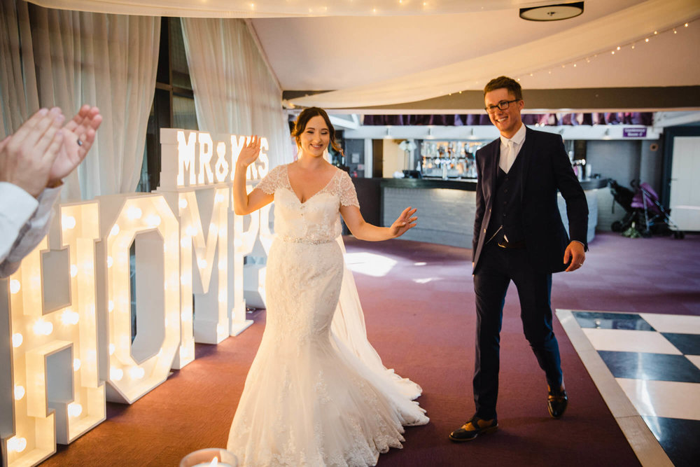 newlyweds dance towards their seats at the top table