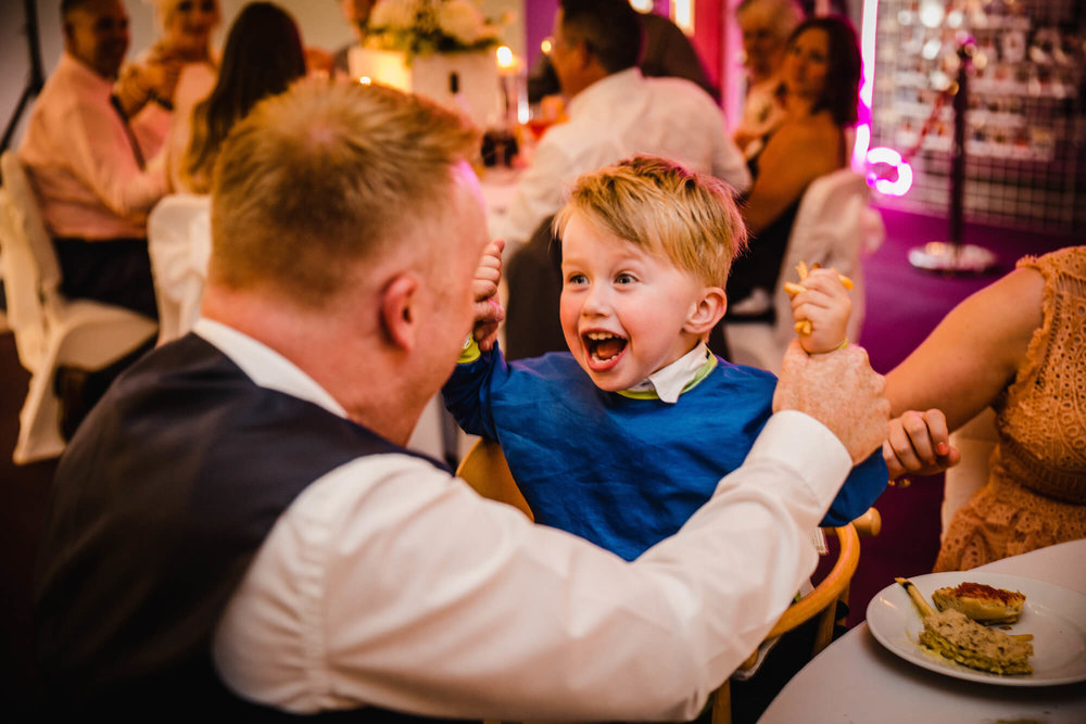 page boy wedding guest cheering with dad at wedding breakfast table