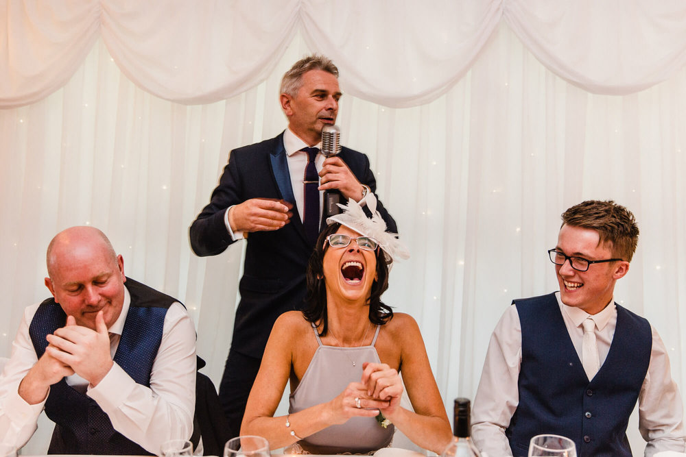 mother of bride laughing out loud on top table with wedding singer paul guard