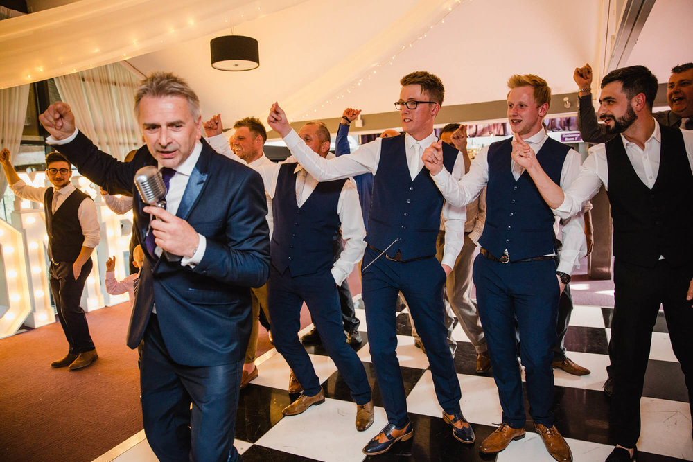 wedding singer paul guard dances with groom and groomsmen on dancefloor