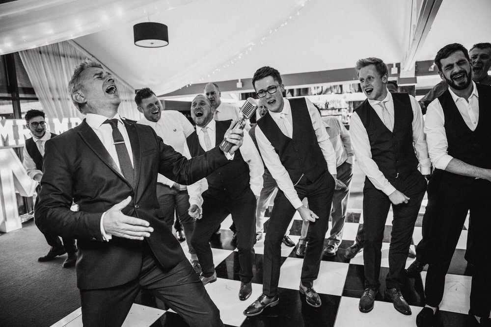 wedding singer paul guard singing with groom and groomsmen on the dance floor at The Waterside Hotel