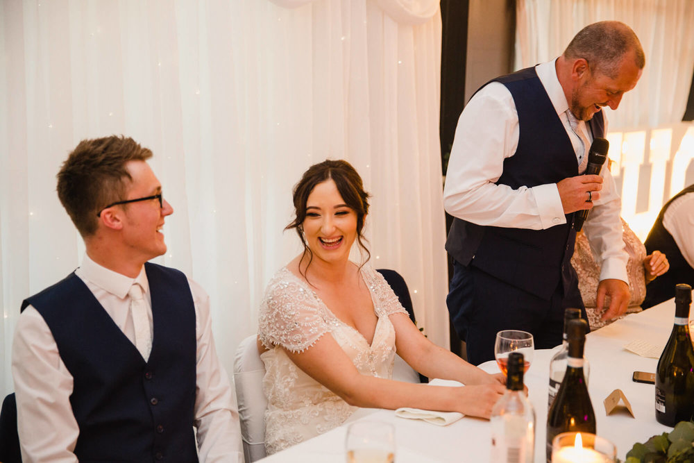 bride laughing at joke during speeches