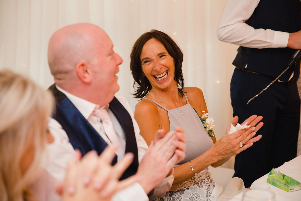 brides mother sharing a joke with her husband during speeches