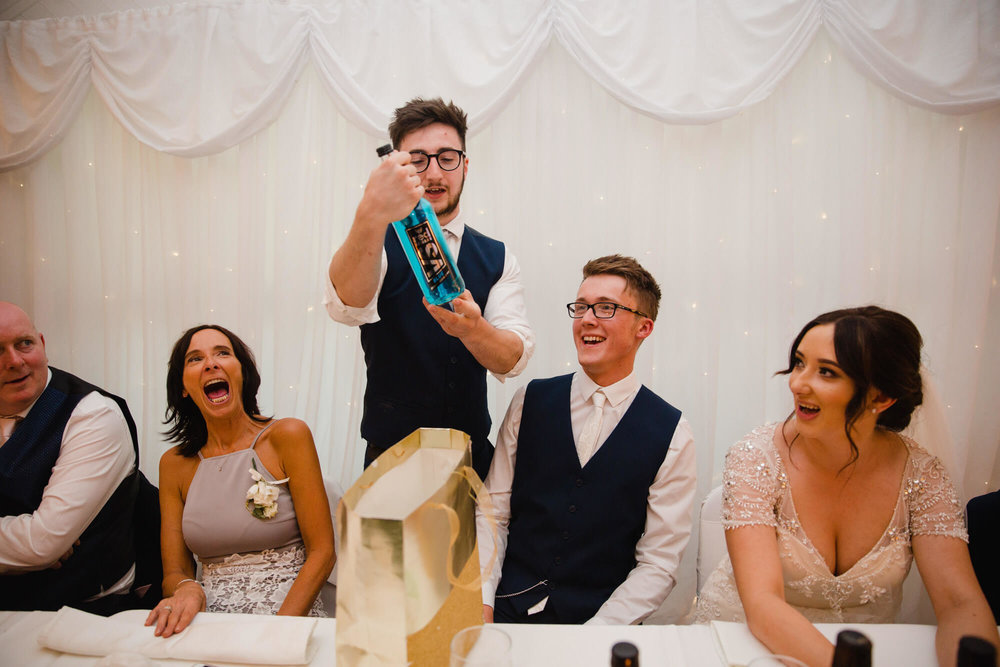 best man giving groom alcoholic drink with family laughing during speeches
