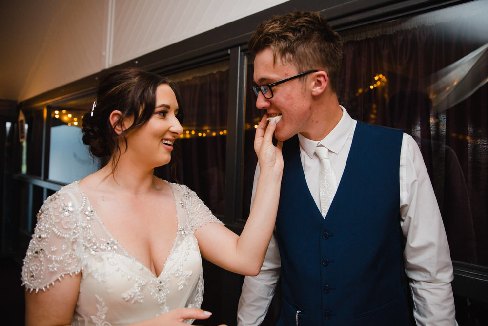 Bride places piece of wedding cake into grooms mouth after cake cutting