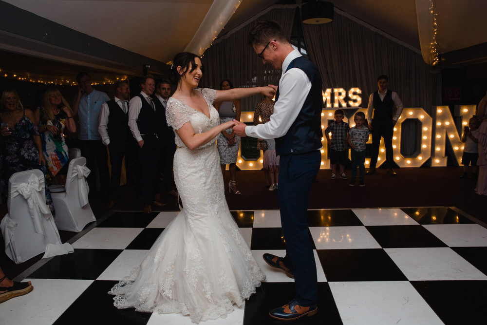 bride and groom dancing on the dance floor for their waterside hotel wedding