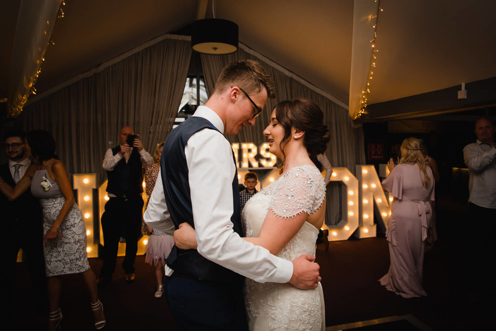 bride and groom sharing intimate moment on dance floor at their waterside wedding