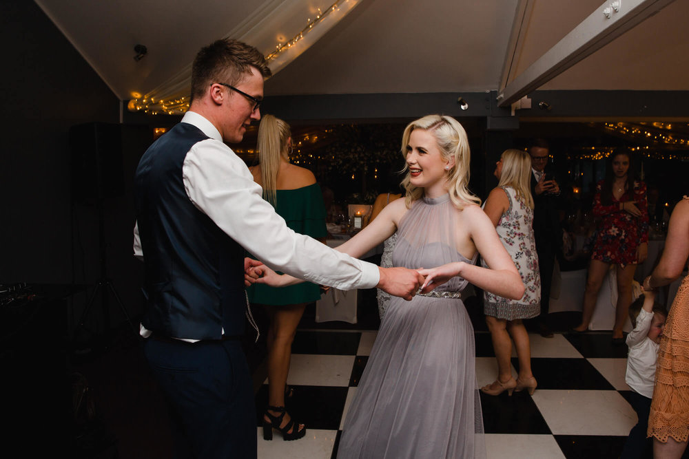 bridesmaid shares a dance with groom