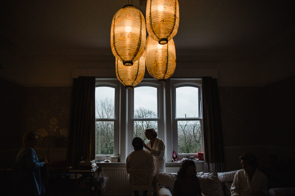 Silhouette photograph of bridal preparation in window at Ashfield House