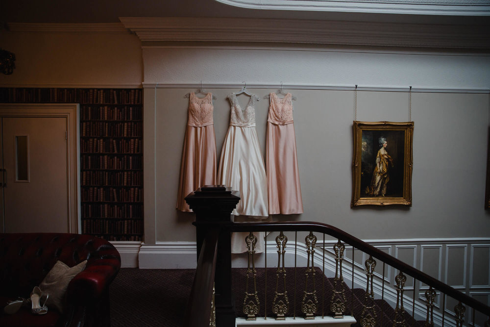 Brides wedding dress hung up on staircase at Ashfield House