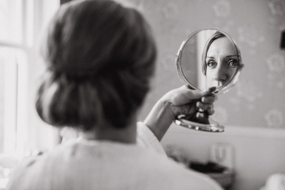 Black and white photograph of brides reflection doing make up in mirror