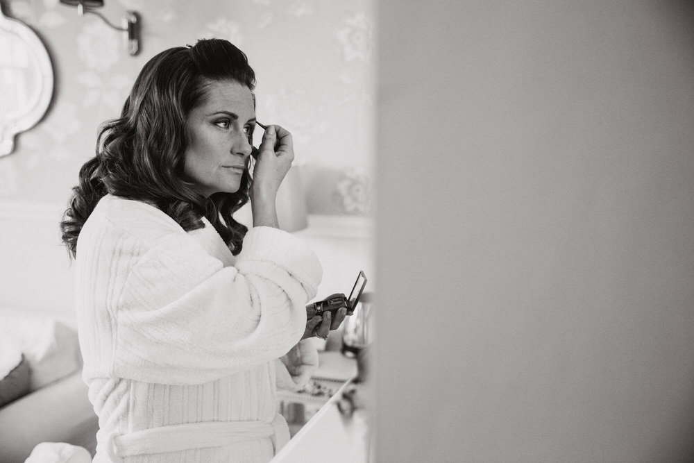 Black and white photograph of bridesmaid having her eyeliner put on in mirror