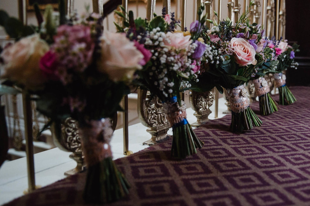 Close up macro photograph of bouquets leaning against bannister of staircase