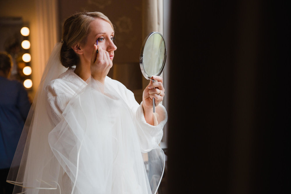 Bride applying mascara in mirror