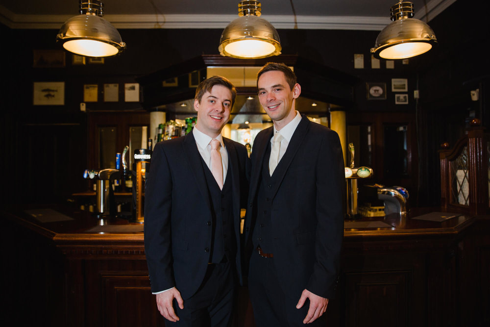 groom and best man pose for photograph at bar of Ashfield House