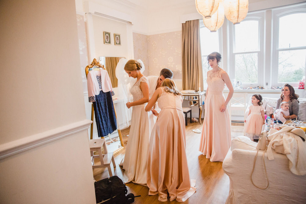 Bride stood in mirror having back of dress fastened by bridesmaids