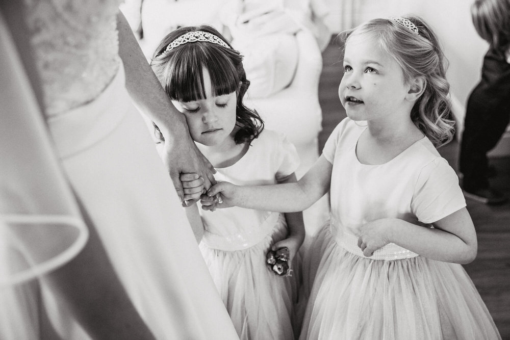Black and white photograph of flower girl with eyes closed holding brides hand