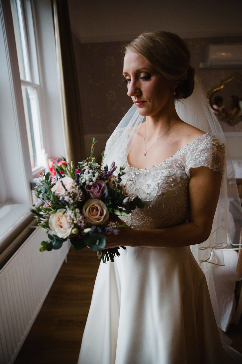 Portrait of bride standing in window holding bouquet