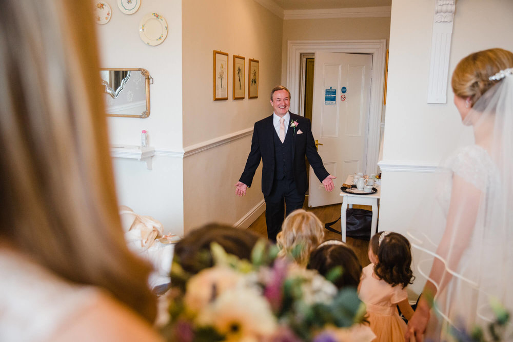 Father of bride enters room with big smile