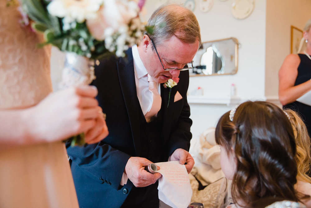 Father of bride reading vows to flower girl