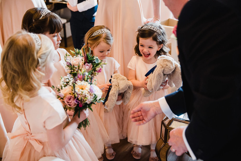 Flower girls laughing together while holding bouquets