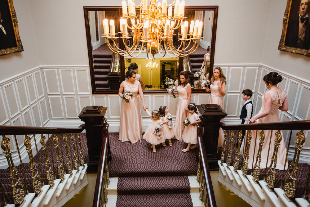 Bridal party walking down staircase of Ashfield House