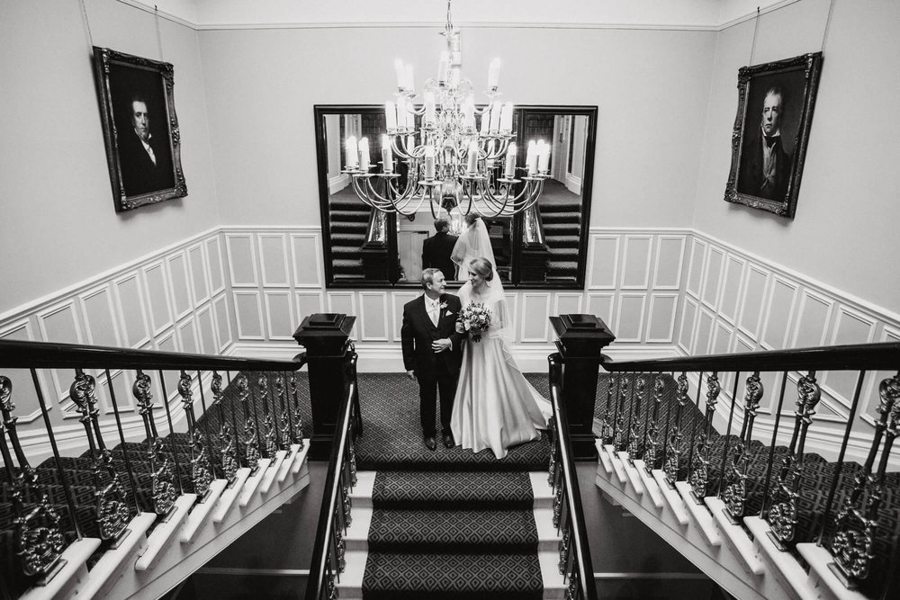 black and white photograph of Bride and father at top of Ashfield House staircase