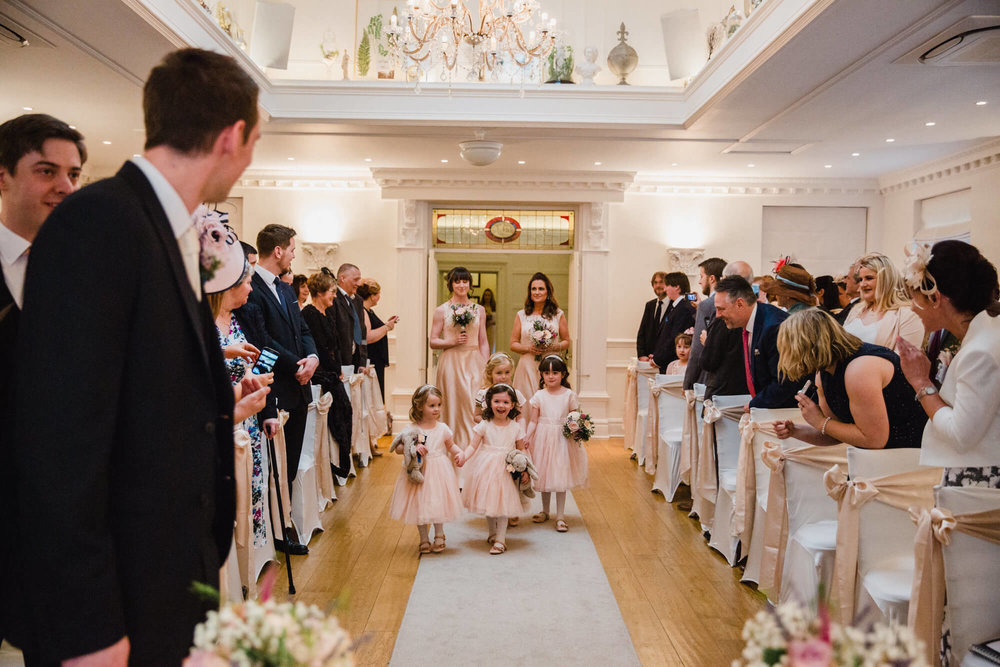 bridesmaids and flower girls walking down aisle at beginning of wedding ceremony
