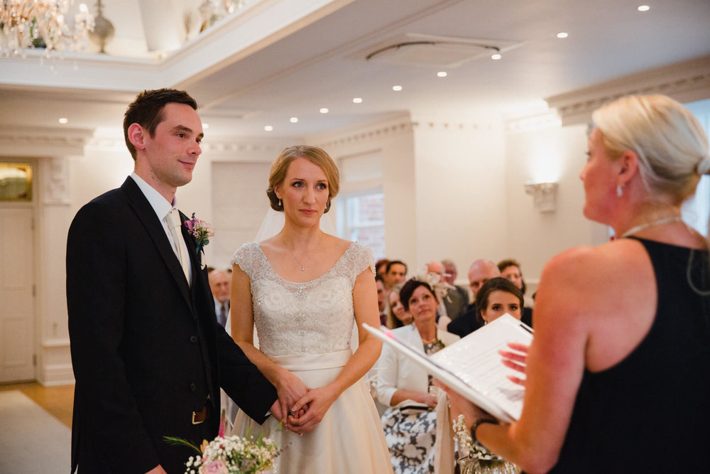bride and groom holding hands while saying their vows at Ashfield House