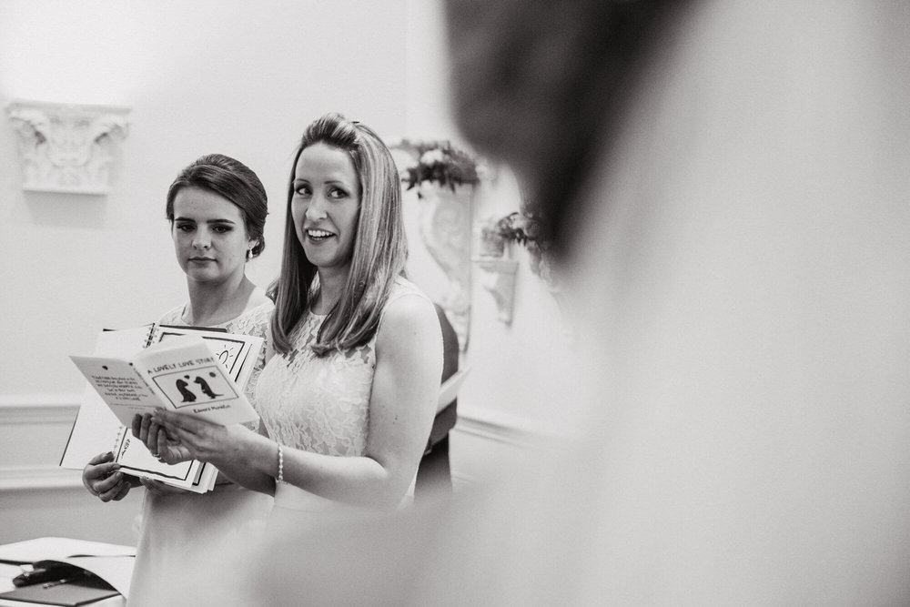 black and white photograph of bridesmaids reading story to bride