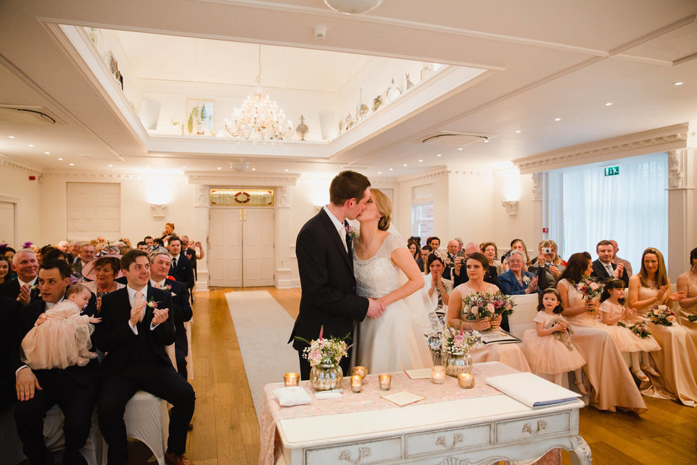 Newlyweds share first kiss at the top of the aisle at Ashfield House