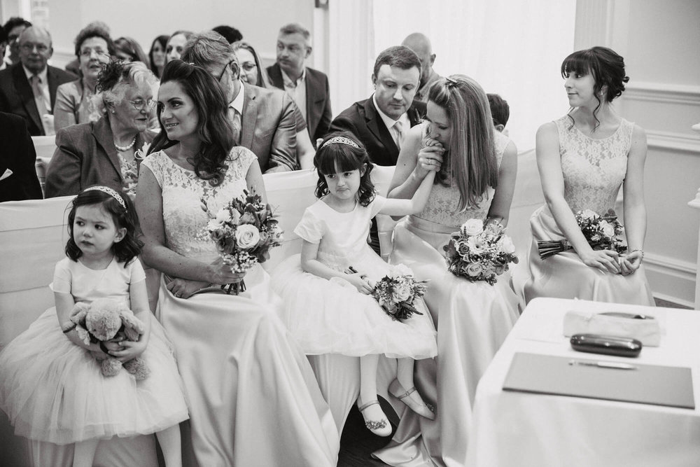 black and white photograph of bridal party on front row of ceremony