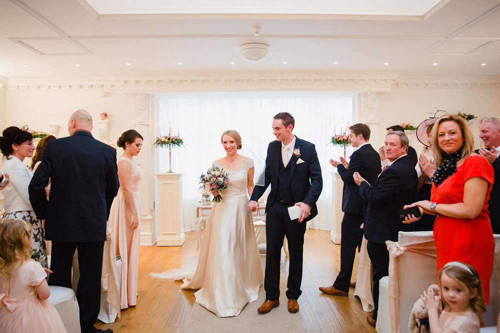 newly married couple walk together down aisle congratulated by family and friends