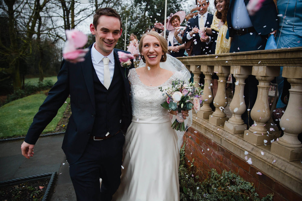 close up of bride and groom laughing under confetti at Ashfield House
